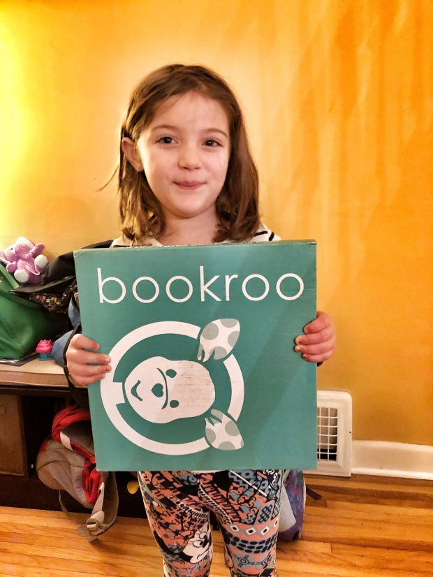 Little girl holding Bookroo box